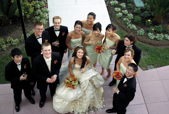 bridesmaids in green dresses and groomsmen pose with bride