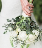 Bride holds bouquet of white roses, greenery and wears diamond wedding bands and engagment ring