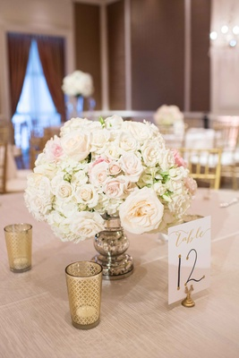 low floral arrangement blush and white little bits of greenery low votives table number tan linen