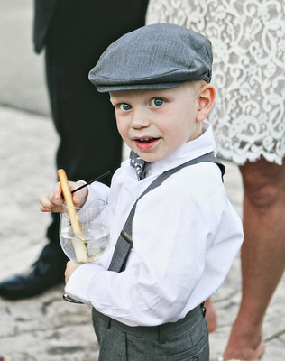 Ring bearer in button down, grey suspenders, pants, newsboy cap and polka dot bow tie holds glass