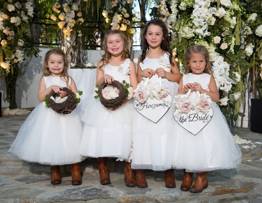 Flower girls in white ball gowns with rustic cowboy boots