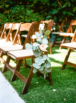 Wedding ceremony outside at lombardi house grass lawn wood folding chair green leaves pink flowers