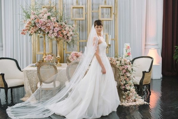 an a-line jinza bridal gown featuring strapless neckline and long veil pink floral arrangements