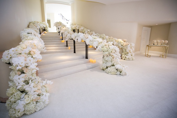 beverly hills hotel wedding entrance stairway with bannisters covered in flowers