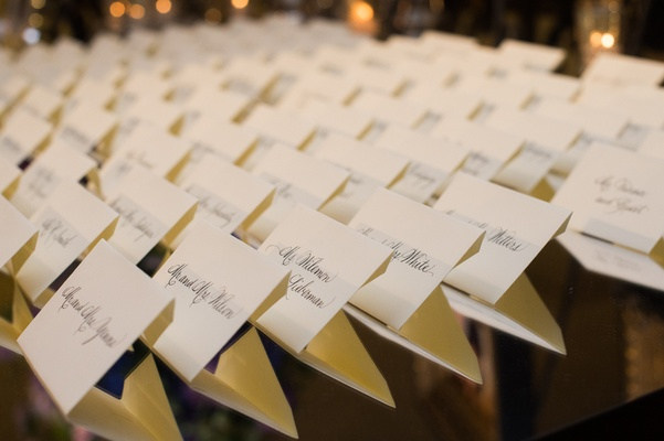 rows of place cards on mirrored table wedding escort cards