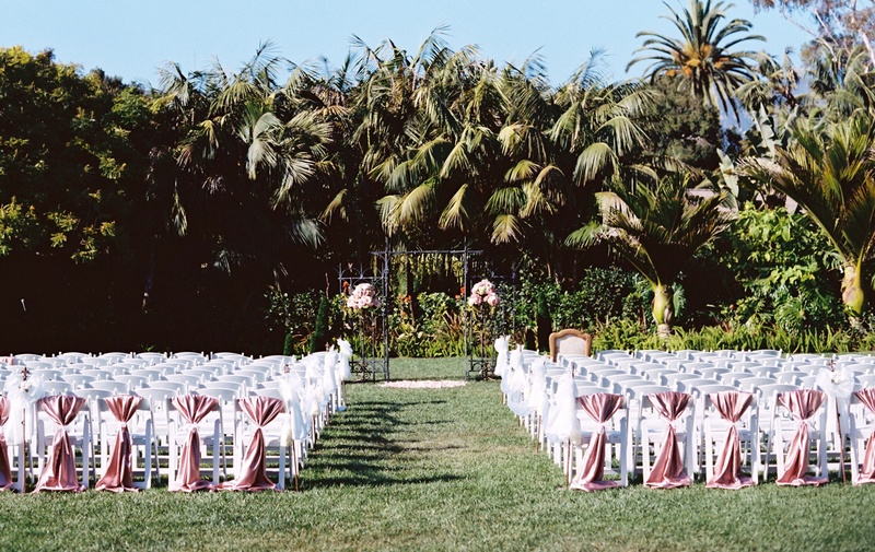 White ceremony chairs greenery arch two flower arrangements pink chair covers on back row