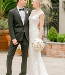 Tall bride and groom smile at each other on wedding day in tuxedo and Reem Acra wedding dress