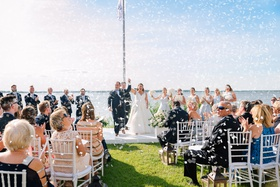 wedding ceremony near water waterfront wedding grass lawn white chair lanterns confetti happy guests