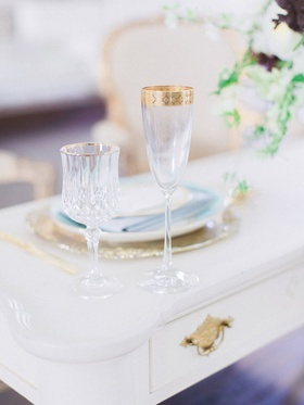 Vintage sweetheart table with gold rimmed wine & champagne glass, gold charger, blue dinner plate