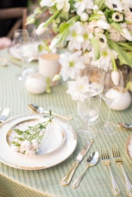 white and gold charger plates with pink flowers on green table linen lush floral arrangement