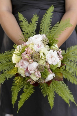 Bridesmaid holding textured flowers with ferns