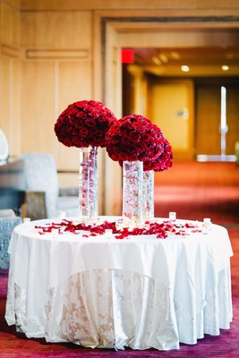 Wedding reception table with red flowers and submerged pink orchid stems in cylinder vases on table