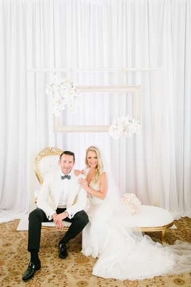 bride in ines di santo gown, groom in white tuxedo jacket, gold and white chaise lounge with frames