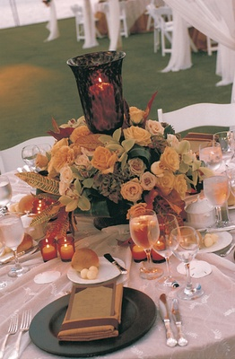 tabletop decor of yellow and green flowers and orange candles