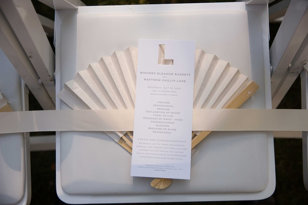 Rectangular wedding ceremony program card with cut out initial at top and fan for hot day