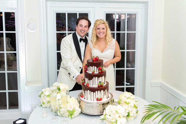 Bride and groom smile with groom's cake Southern white cake chocolate ganache dripping down berries