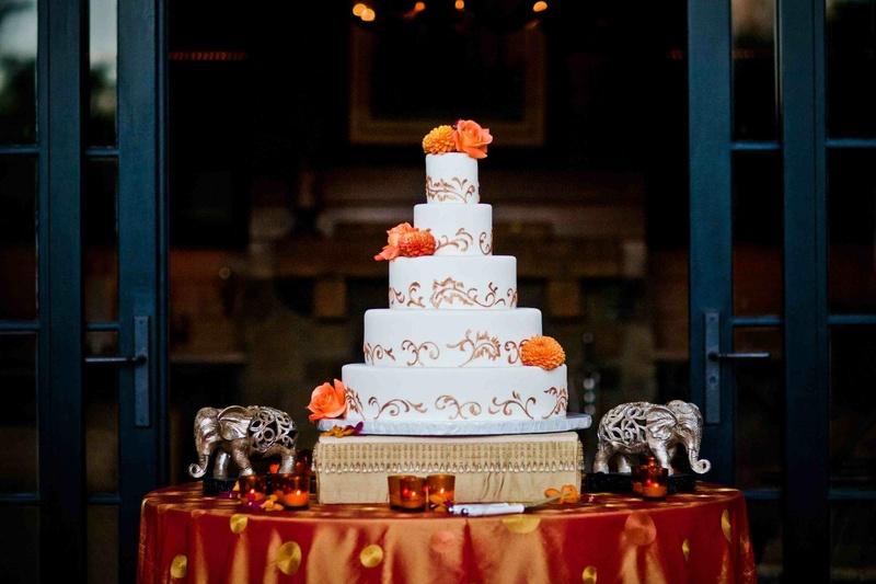 White wedding cake with golden swirls and fresh orange flowers