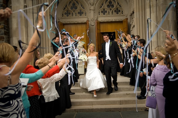 guests wave ribbons as newlyweds walk past