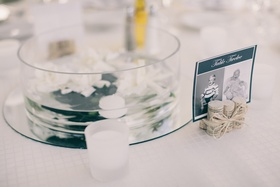 Wedding reception table with white gardenias and candles floating in round vase on top of a mirror