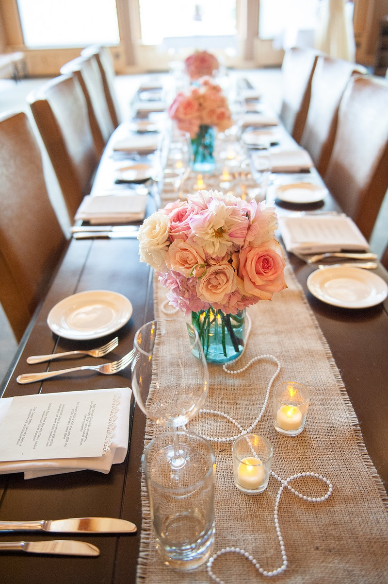 Burlap table runner with pink and white roses in blue mason jar and pearls