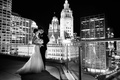 Black and white photo of bride in Monique Lhuillier wedding dress and groom with Chicago skyline