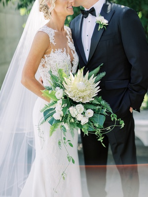 bride holding large bouquet with ivory king protea flower tropical greenery illusion wedding dress