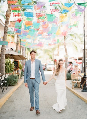 Bride in spaghetti strap v neck wedding dress groom in grey suit light blue under fiesta flags mexic