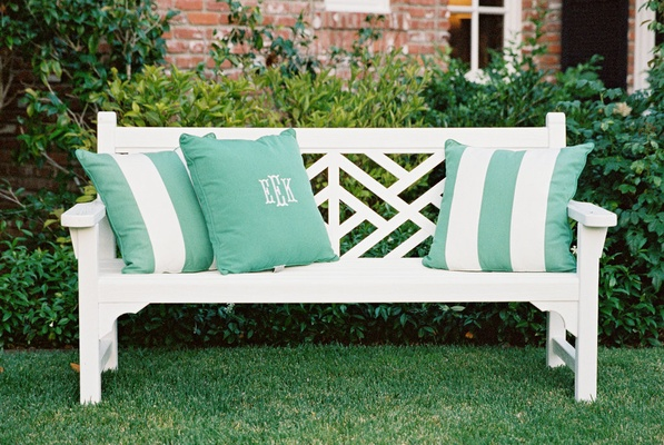 White lounge furniture with green and white stripe pillows and monogram pillow