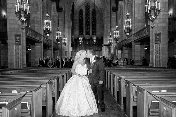 Black and white photo of bride in an Ines Di Santo gown kissing groom in black tux in church aisle