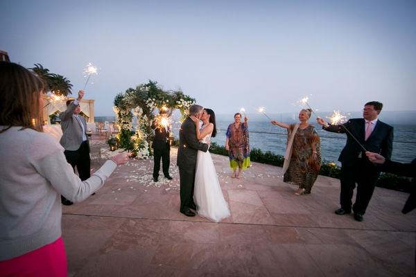 Bride and groom kiss at santa barbara resort guests holding sparklers sunset kiss wedding ideas
