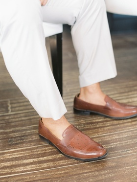Brown leather shoes and no socks on groom with light colored pants