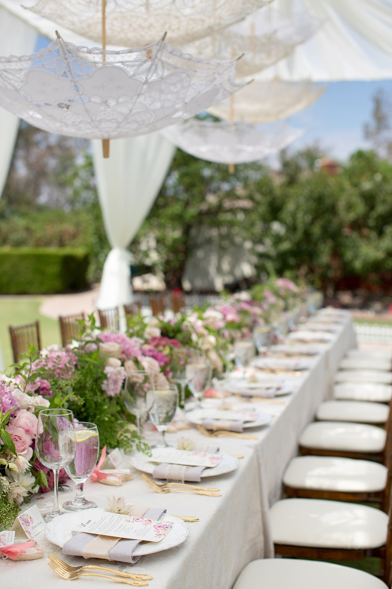 gold flatware at bridal shower with long table pastel flower arrangements and lace parasols