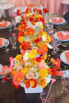 Bright yellow pink red poppy flowers in white square vase with pink glassware wood table shower