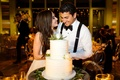 Bride and groom cut into two layer wedding cake white with fresh flowers on top rustic elegant cake
