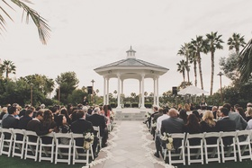 White chairs facing gazebo and ocean view