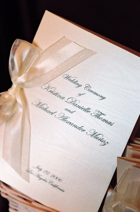 Wedding program tied with white and ivory ribbon
