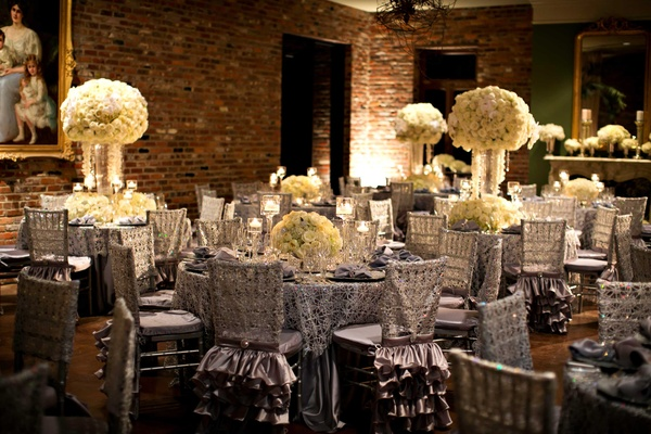 Reception room with brick wall, paintings, and silver tables with white centerpieces