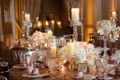 Wedding reception table with pink and white flowers, pillar candles in crystal hurricanes