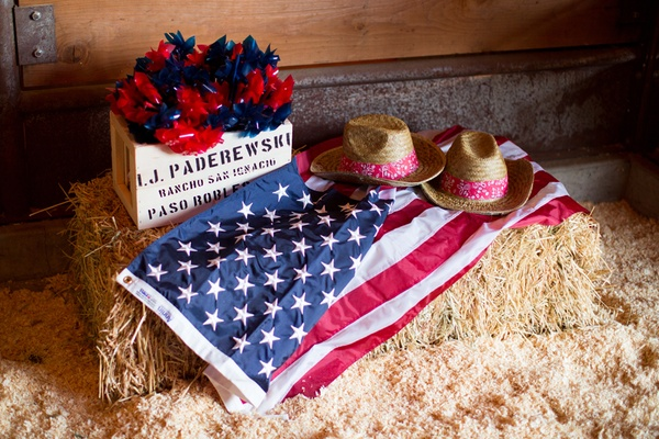 Wooden box of blue and red pinwheels on top of hay bale with american flag and cowboy hats