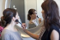 Woman putting makeup on bride in bridal suite
