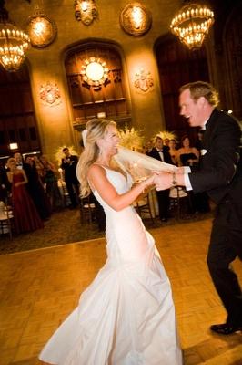 Bride in a spaghetti strap gown dances with groom in black tuxedo