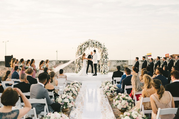wedding ceremony flower wall white shiny aisle runner low flowers in gold urns colombia outdoor