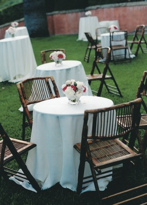 White cocktail tables surrounded by tropical brown seating