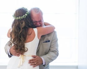 Bride in flower crown hugs crying father of the bride
