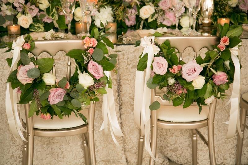 Roses, garland & ribbon make for beautiful bride & groom chair decor.