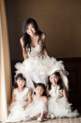 flower girls posing underneath bridal gown white fluffy sweet cute moment california wedding