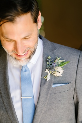 groom in grey suit and light blue tie, wildflower boutonniere