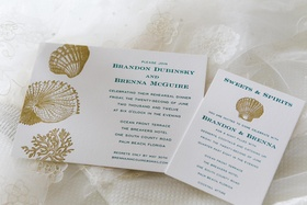 white invitations with blue print and gold seashells