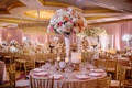 wedding reception round table tall centerpiece white vase ivory hydrangea pink coral rose gold chair