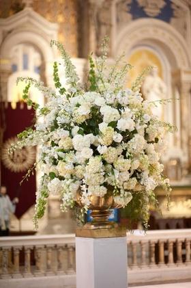 White flowers in gold urn vase at Catholic ceremony